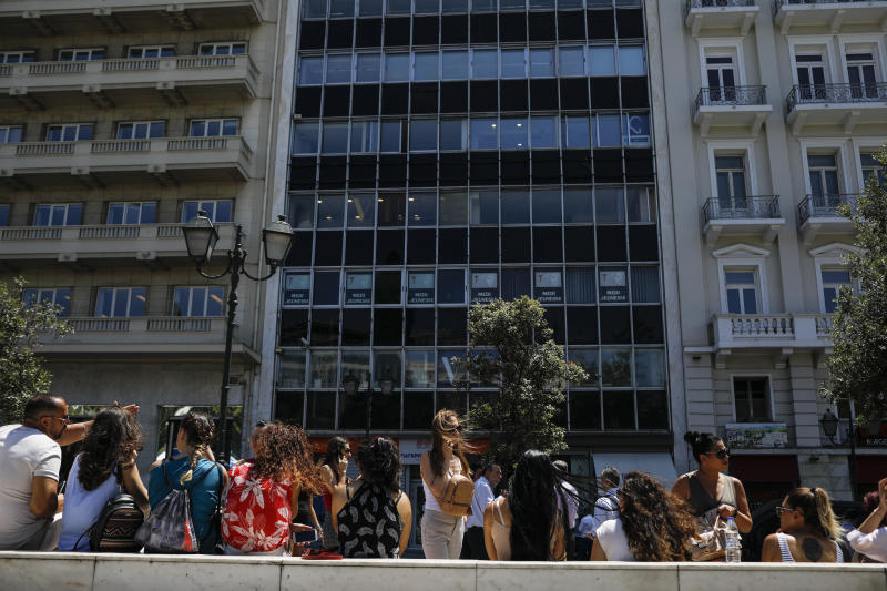 People speak on their phones as they stand outside the building they work in with the Greek Parliament in the background, after a strong earthquake hit near the Greek capital of Athens, Friday, July 19, 2019. The Athens Institute of Geodynamics gave the earthquake a preliminary magnitude of 5.1 but the U.S. Geological Survey gave it a preliminary magnitude of 5.3. The Athens Institute says the quake struck at 2:38 p.m. local time (1113 GMT) about 26 kilometers (13.7 miles) north of Athens. (AP Photo/Petros Giannakouris)