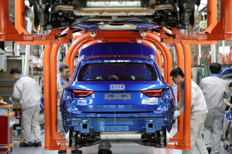 Workers work on an assembly line manufacturing Audi Q3 cars at the FAW-Volkswagen Tianjin plant in Tianjin