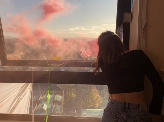 Students let off flares after occupying Manchester University's Owens Park Tower (PA)
