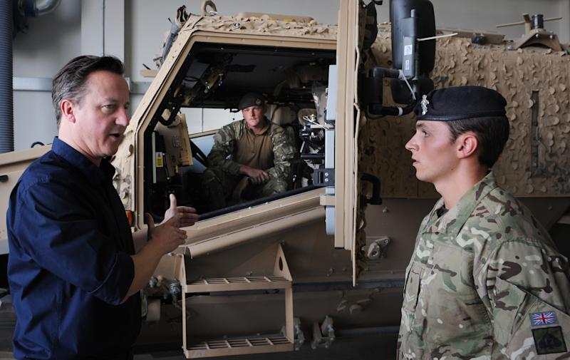 Britain's Prime Minister, David Cameron, left, is shown a new 'Foxhound' armoured vehicle by unidentified British soldiers at Camp Bastion in Afghanistan, Wednesday, July 18, 2012 during a surprise trip to the area. Earlier he met Afghan National Police chiefs. (AP Photo/Stefan Rousseau, Pool)