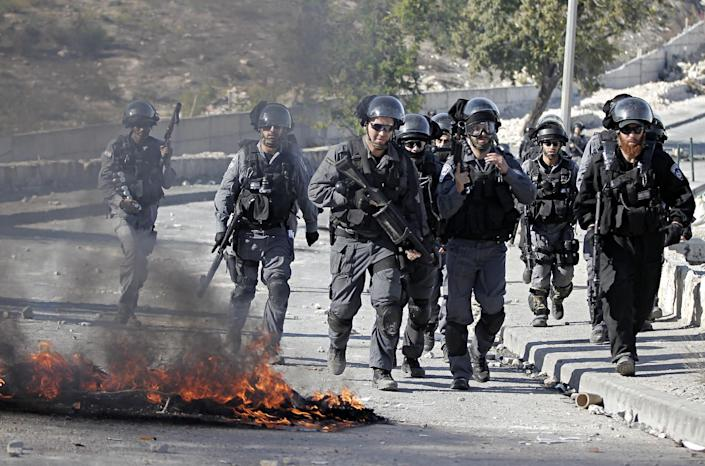 Israeli security officers run past burning tires during clashes with Palestinian protesters in the Issawiya district of Arab east Jerusalem on October 24, 2014 (AFP Photo/Ahmad Gharabli )