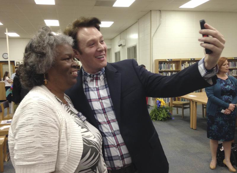 Democratic nominee Clay Aiken takes a pictures with a constituent after a campaign forum in Cary, North Carolina