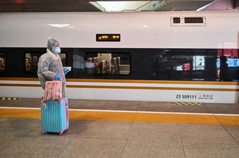 A woman wearing protective gear as she boards a train stopping at Wuhan, which has opened stations again to incoming passengers