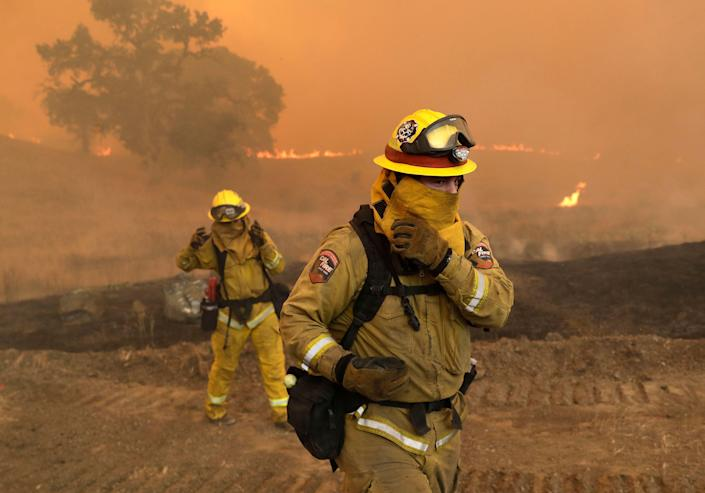 Firefighters with Cal Fire Mendocino Unit cover themselves from smoke and ash created by an advancing wildfire in Lakeport.