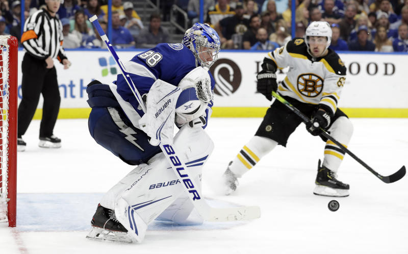 Tampa Bay Lightning goaltender Andrei Vasilevskiy (88) makes a save on a shot by the Boston Bruins during the third period of an NHL hockey game Monday, March 25, 2019, in Tampa, Fla. Looking for a rebound is Bruins' Brad Marchand. (AP Photo/Chris O'Meara)