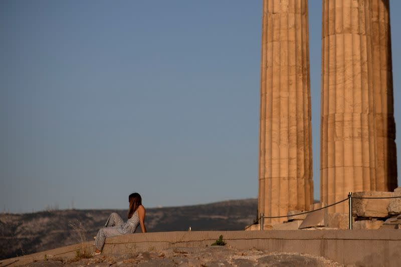 FILE PHOTO: A woman rests on a new cement walkway next to the Parthenon temple, built to improve access for people with disabilities atop the Acropolis hill, in Athens