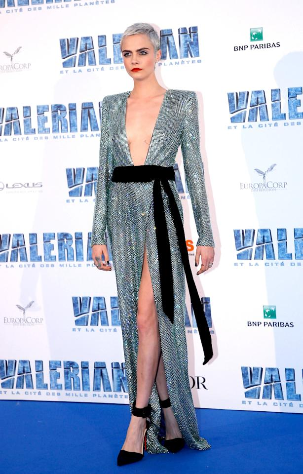 <p>Delevingne chose a plunging silver gown from Alexandre Vauthier. The flashy design, which Bella Hadid actually wore down the runway, featured a black sash and an even more revealing thigh-high slit. (Photo: Getty Images) </p>