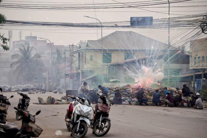 Firecrackers explode as protestors take cover behind a barricade during a demonstration against the military coup in Mandalay