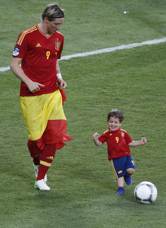Spain's Fernando Torres (L) plays a ball with his son Leo after defeating Italy to win the Euro 2012 final soccer match at the Olympic stadium in Kiev, July 1, 2012.     REUTERS/Charles Platiau (UKRAINE  - Tags: SPORT SOCCER TPX IMAGES OF THE DAY)