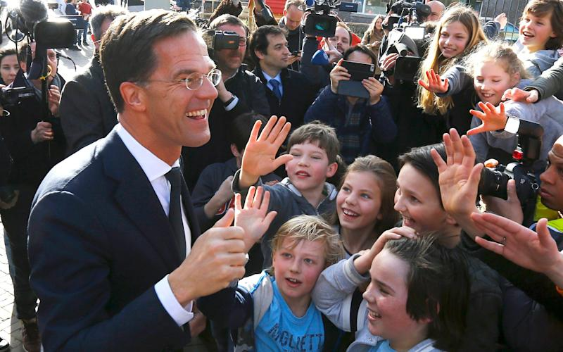 Dutch Prime Minister Mark Rutte of the VVD party greets supporters after voting in the general election in The Hague - reuters