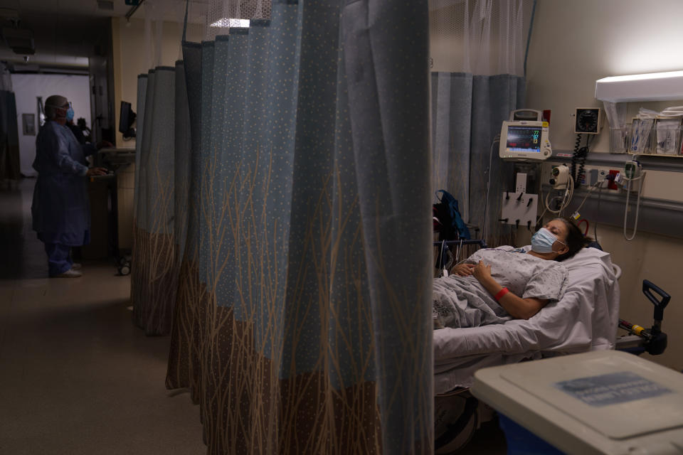 A patient, who declined to give her name, waits for the result of her COVID-19 test in an emergency room at Providence Holy Cross Medical Center in the Mission Hills section of Los Angeles, Tuesday, Dec. 22, 2020. (AP Photo/Jae C. Hong)