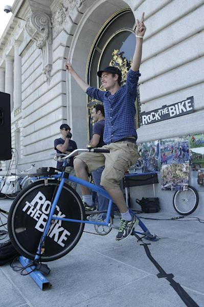 """Jakob von Essen, who came from Sweden to intern with Bay Area Green Tours, gestures toward a crowd as he rides a Rock The Bike """"One Bike/One Speaker,"""" a bicycle that generated power for the sound system at rally to support fossil fuel divestment outside of City Hall in San Francisco, Thursday, May 2, 2013. (AP Photo/Jeff Chiu)"""