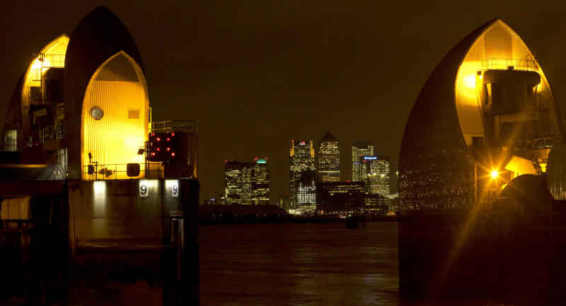 FILE - The financial center of Canary Wharf just outside the boundary of the City of London is seen through the Thames Barrier at night on Friday, Dec. 28, 2012. The low-lying city has long been vulnerable to flooding - particularly when powerful storms send seawater racing up the River Thames. But the 570-yard-long (half-a-kilometer-long) barrier, composed of 10 massive steel gates, each five stories high when raised against high water, has been in operation since 1982. (AP Photo/Alastair Grant, File)