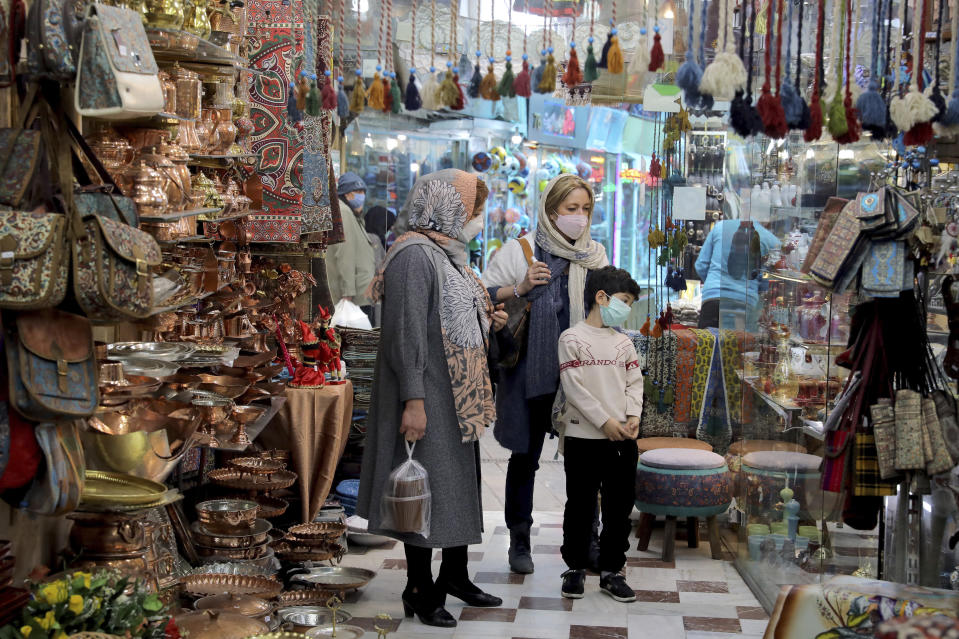 """Mask-clad shoppers look at items in a shop ahead of the Persian New Year, or Nowruz, meaning """"New Day."""" in northern Tajrish traditional bazaar, in Tehran, Iran, Wednesday, March 17, 2021. (AP Photo/Ebrahim Noroozi)"""