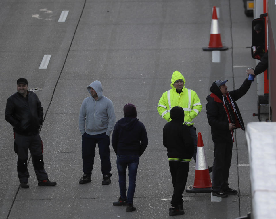 Drivers walk on the motorway as their trucks are parked up on the M20, as more arrive to join the queue, part of Operation Stack in Ashford, Kent, England, Friday, Dec. 25, 2020. Thousands wait to resume their journey across The Channel after the borders with France reopened. Trucks inched slowly past checkpoints in Dover and headed across the Channel to Calais on Thursday after France partially reopened its borders following a scare over a rapidly spreading new virus variant. (AP Photo/Kirsty Wigglesworth)