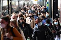 Commuters pour into Milan at the Cardona railway station after months of stop-start coronavirus curbs
