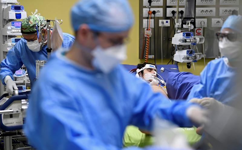 SENSITIVE MATERIAL. THIS IMAGE MAY OFFEND OR DISTURB Multiple members of the medical staff in protective suits treat an 18-year old patient suffering from coronavirus disease (COVID-19) in an intensive care unit at the San Raffaele hospital in Milan, Italy, March 27, 2020. REUTERS/Flavio Lo Scalzo