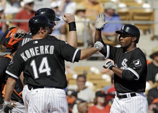 Chicago White Sox's Dewayne Wise, right, is welcomed home by Paul Konerko (14) and Adam Dunn after they score on Wise's three-run home run in the fourth inning of an exhibition spring training baseball game against the San Francisco Giants Monday, March 4, 2013, in Glendale, Ariz. (AP Photo/Mark Duncan)
