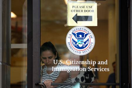 FILE PHOTO: A woman leaves the U.S. Citizenship and Immigration Services offices in New York, August 15, 2012. REUTERS/Keith Bedford/File Photo