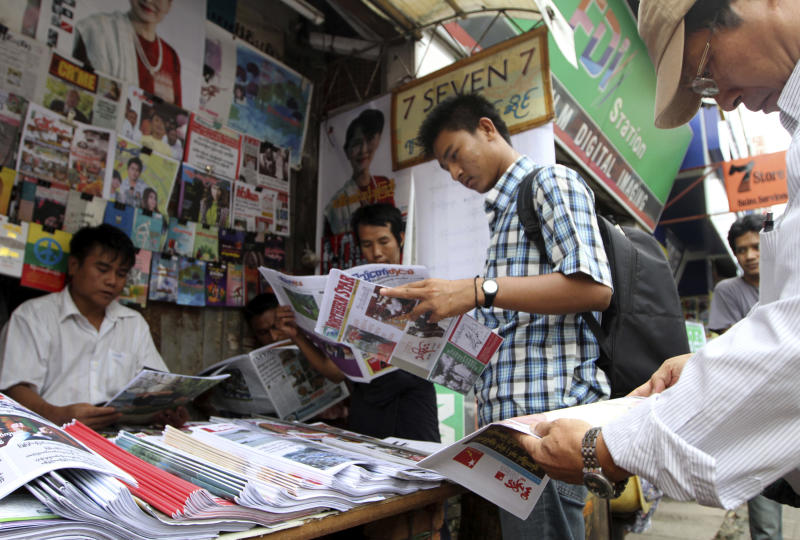 Customers buy local weekly journals at a roadside shop in Yangon, Myanmar, Monday, Aug. 20, 2012. Myanmar's government said Monday it was abolishing the harsh practice of directly censoring the country's media, the most dramatic move yet toward allowing freedom of expression in the long-repressed nation. Under the new rules, journalists will no longer have to submit their work to state censors before publication as they for almost half a century. (AP Photo/Khin Maung Win)