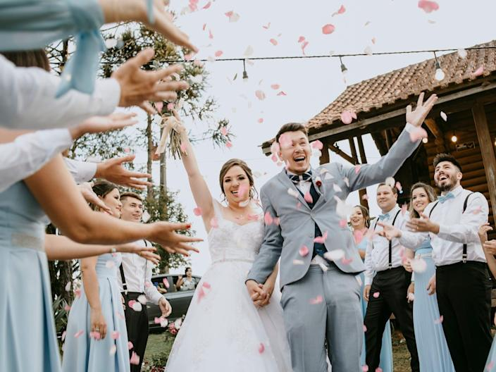 A bride and groom walk between their bridal party as they throw flower petals.
