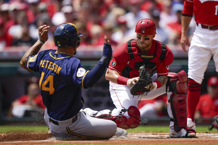 Milwaukee Brewers' Jace Peterson (14) is tagged out at home by Cincinnati Reds catcher Tucker Barnhart during the first inning of a baseball game in Cincinnati, Sunday, July 18, 2021. (AP Photo/Bryan Woolston)