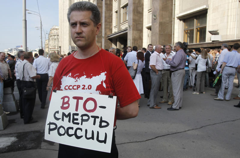 "A Communist supporter pickets parliament headquarters with a poster reading: ""WTO is Death for Russia"" in Moscow, Russia, Tuesday, July 10, 2012. Russia's parliament is due to ratify an agreement for Russia to join the World Trade Organization in a move that will push Moscow to open up its economy. (AP Photo/Misha Japaridze)"