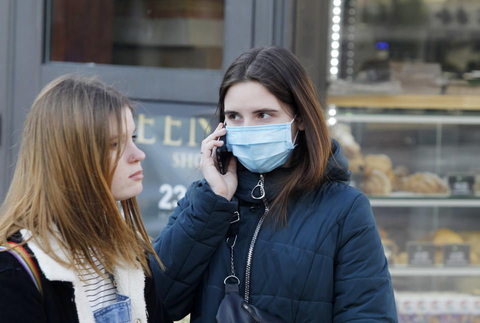 An young woman wearing a protective face mask as a preventive measure against corona virus uses a mobile phone in the street.