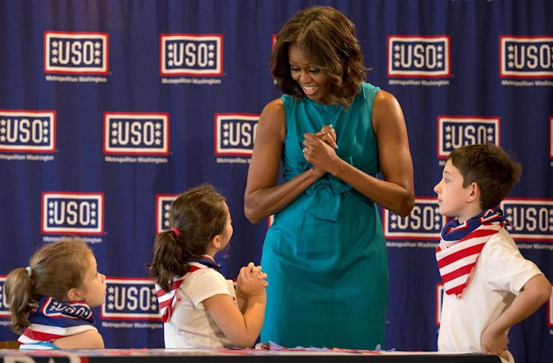 A girl mimics first lady Michelle Obama's body language as she visits with children at the USO Warrior and Family Center in Fort Belvoir, Va., Wednesday, Sept. 11, 2013, during a service project to commemorate the Sept. 11th National Day of Service and Remembrance at Food and Friends. (AP Photo/Jacquelyn Martin)