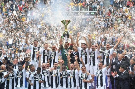 Juventus goalie Gianluigi Buffon holds up the Serie A soccer title trophy, at the Allianz Stadium in Turin, Italy, Saturday, May 19, 2018. Juventus beat already relegated Hellas Verona 2-1 in the final round of the season on Saturday but the result mattered little as the club bid an emotional farewell to Buffon, while it also received a record-extending seventh successive Serie A trophy. (Alessandro Di Marco/ANSA via AP)