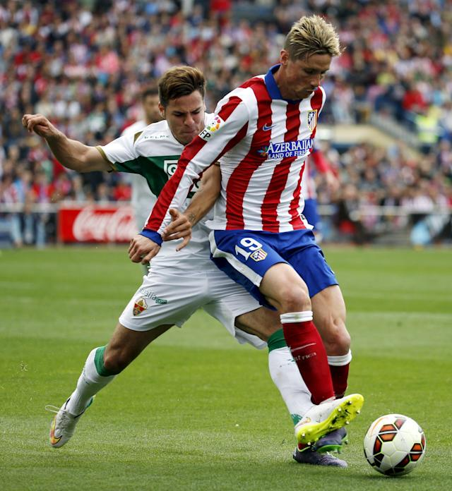 Atletico Madrid's Fernando Torres (R) fights for the ball with Elche's Samuel Martinez during their Spanish first division soccer match at Vicente Calderon stadium in Madrid, April 25, 2015. REUTERS/Susana Vera