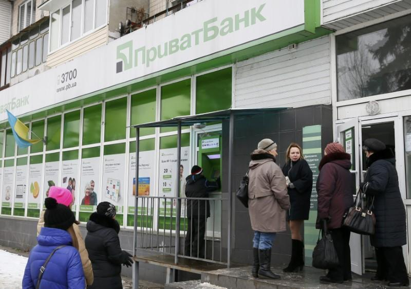 People gather near an automated teller machine outside a PrivatBank branch in Kiev