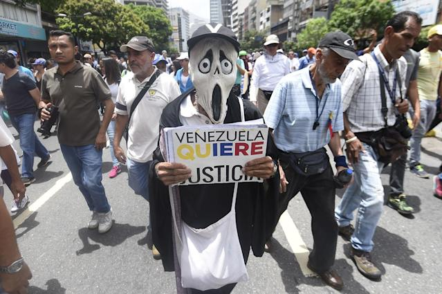 <p>Opposition activists march in Caracas on May 22, 2017.<br> Doctors rallied in Venezuela on Monday in the latest street protests against the government of President Nicolas Maduro, as a young man lay in hospital after being set on fire by an angry crowd. (Photo: Juan Barreto/AFP/Getty Images) </p>