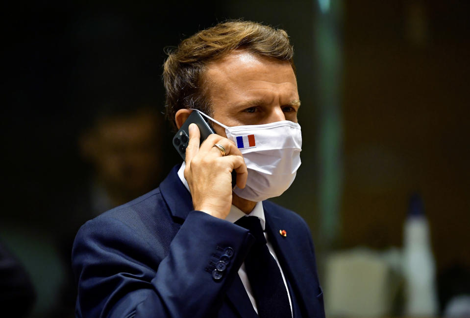 FILE - In this Monday, July 20, 2020 file photo, French President Emmanuel Macron speaks on his mobile phone during a round table meeting at an EU summit in Brussels. French newspaper Le Monde is reporting that the cellphones of French President Emmanuel Macron and 15 members of the French government in 2019 may have been among potential targets of surveillance by spyware made by the Israel-based NSO Group. The Paris prosecutor's office announced Tuesday, July 20, 2021 it is investigating the suspected widespread use of the Pegasus spyware to target journalists, human rights activists and politicians in multiple countries. (John Thys, Pool Photo via AP, File)