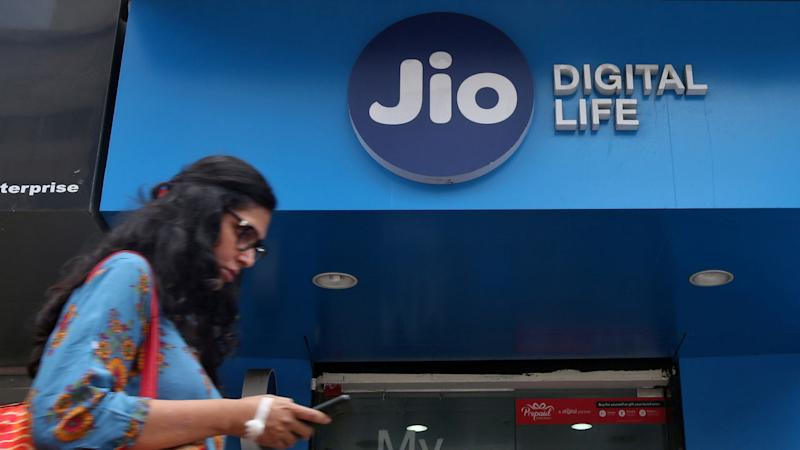 A woman checks her mobile phone as she walks past a mobile store of Reliance Industries' Jio telecoms unit, in Mumbai, India, July 11, 2017. REUTERS/Shailesh Andrade - RC1E582C9B50
