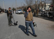 Zabiullah Doorandish, center, who works for a local TV channel in Kabul, arrives at the site of a blast in Kabul, Afghanistan, Tuesday, Feb. 9, 2021. Doorandish survived a roadside bomb attack by the Islamic State last May. He says now he lives much of the time in fear. Like many journalists he gets death threats, but he says he isn't sure who is behind them, even though some say they are Taliban. (AP Photo/Rahmat Gul)