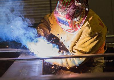 A welder works on infrastructure for a hydropower plant undergoing rehabilitation.