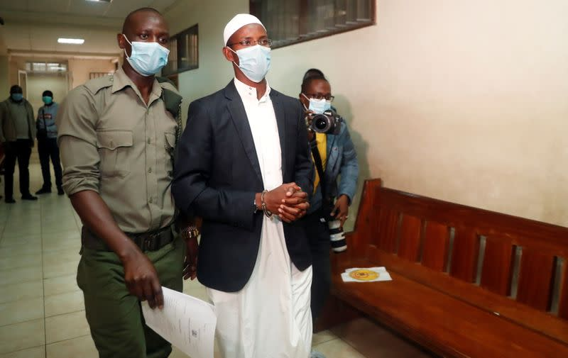Mohamed Ahmed, a suspect charged with helping al Qaeda-linked militants to launch an attack on the Westgate mall, is escorted by a security officer after his sentencing, at the Milimani Law Courts in Nairobi