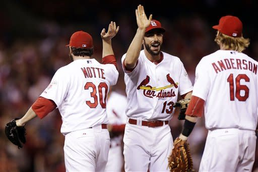 St. Louis Cardinals third baseman Matt Carpenter, center, celebrates with closer Jason Motte and first baseman Bryan Anderson against the Cincinnati Reds after the final out of their baseball game, Wednesday, Oct. 3, 2012, in St. Louis. The Cardinals won 1-0. (AP Photo/St. Louis Post-Dispatch, Chris Lee) EDWARDSVILLE INTELLIGENCER OUT; THE ALTON TELEGRAPH OUT