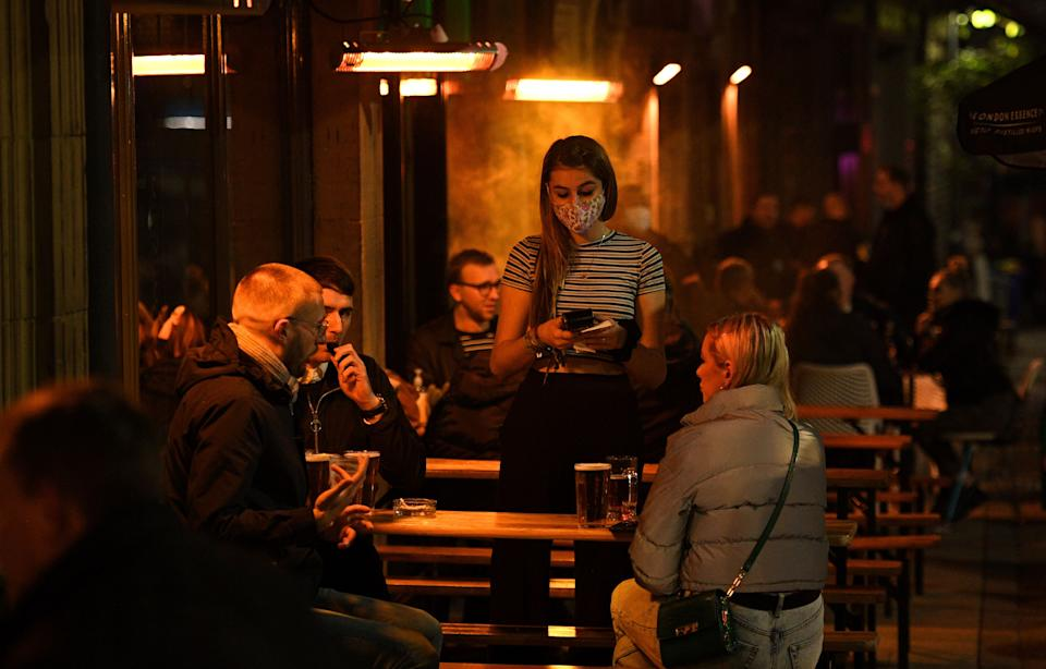A waitress wearing a face mask or covering due to the COVID-19 pandemic, takes customers' orders as they sit outside a bar in Leeds, northern England on November 4, 2020, on the eve of a second novel coronavirus COVID-19 lockdown in an effort to combat soaring infections. - English pubs call last orders at the bar for a month on Wednesday evening, as the country effectively shuts down from November 5, for the second time this year to try to cut coronavirus cases. Prime Minister Boris Johnson insisted that the lockdown for England would end
