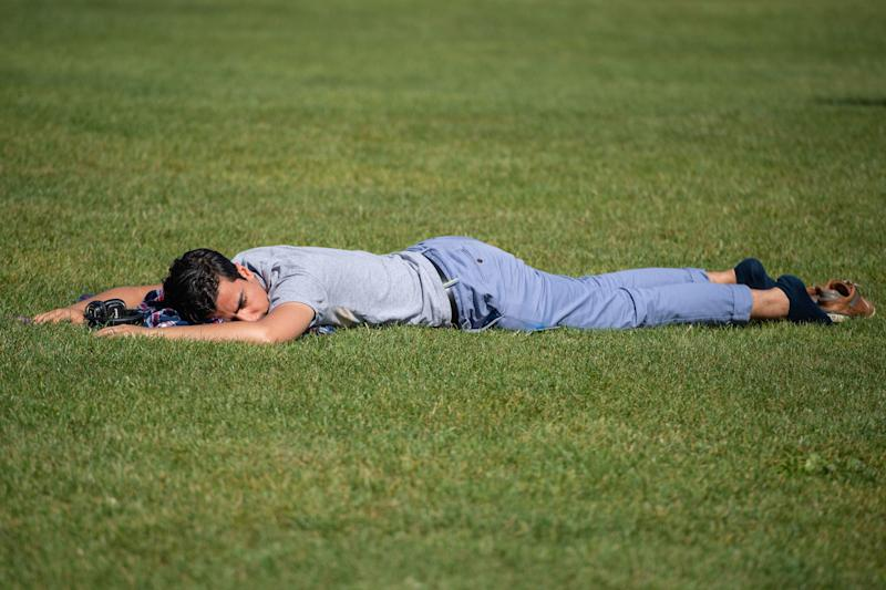 A man relaxes on the grass as he enjoys a period of sunshine on Primrose Hill in London on Saturday (Picture: PA)