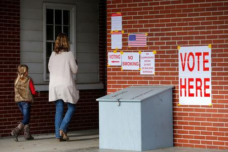Anna Atkinson walks into a polling station with her 8-year-old daughter Tori, in Gallant, Alabama, U.S., December 12, 2017.  REUTERS/Jonathan Bachman