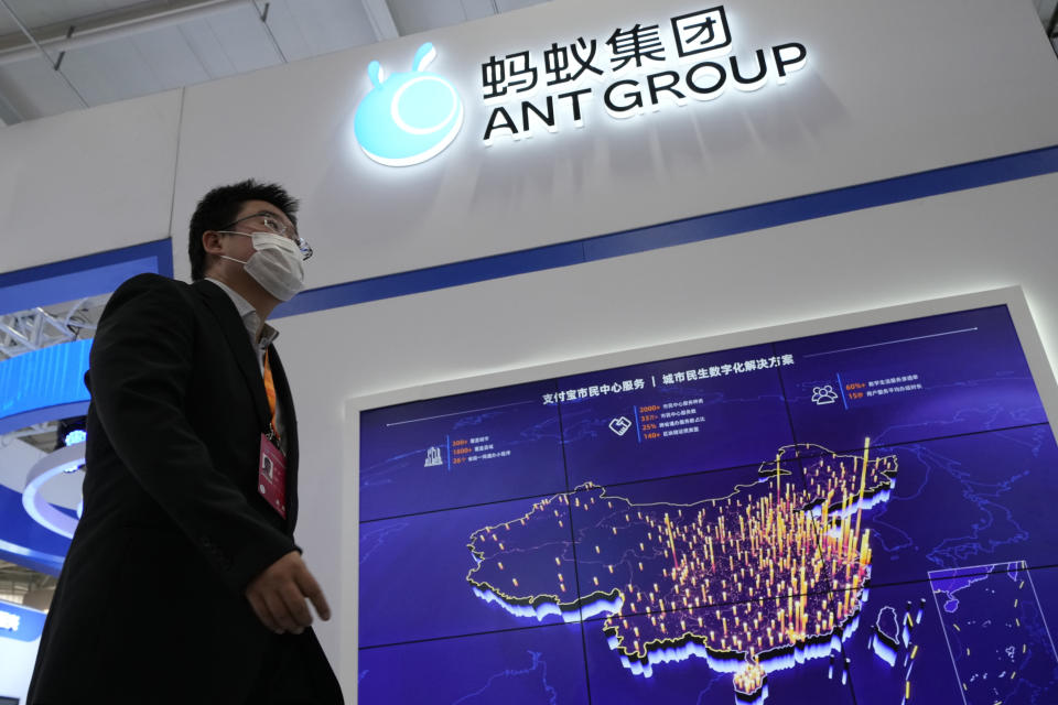 A visitor to a trade fair pasts by the Ant Group booth in Beijing, China, Monday, Sept. 6, 2021. China's central bank will soon have access to private credit information of hundreds of millions of users of Ant Group's online credit service, in a move signaling more regulatory oversight of the financial technology sector. (AP Photo/Ng Han Guan)