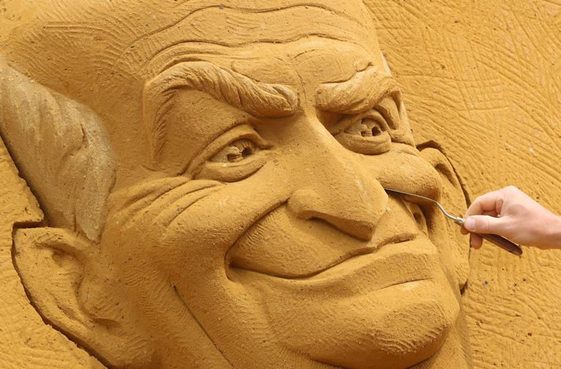 "A sand carver works on a sculpture depicting French actor Louis de Funes, during the Sand Sculpture Festival ""Dreams"" in Ostend, Belgium June 18, 2019. (Photo: Yves Herman/Reuters)"