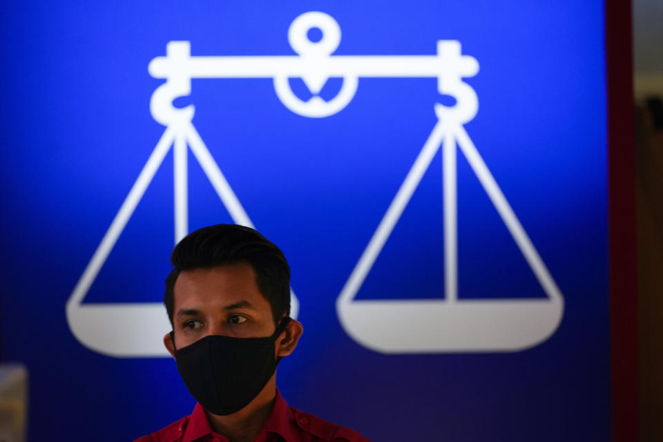 A man wearing a face mask to help curb the spread of the coronavirus stands in front of National Front coalition poster at UMNO headquarter in Kuala Lumpur, Malaysia, Monday, Oct. 26, 2020. A key ally has reaffirmed support for Malaysian Prime Minister Muhyiddin Yassin's government, offering him a respite after his failed bid to declare a coronavirus emergency, but his political survival still hangs in the balance. The UMNO, the biggest party in the unelected governing coalition was angry at being sidelined amid rivalry with Muhyiddin's own Malay party. (AP Photo/Vincent Thian)