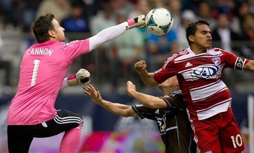 Vancouver Whitecaps goalkeeper Joe Cannon, left, punches the ball away from FC Dallas' David Ferreira, right, of Colombia, as Whitecaps' Alain Rochat, back, defends during the first half of an MLS soccer game in Vancouver, British Columbia on Saturday April 27, 2013. (AP Photo/The Canadian Press, Darryl Dyck)
