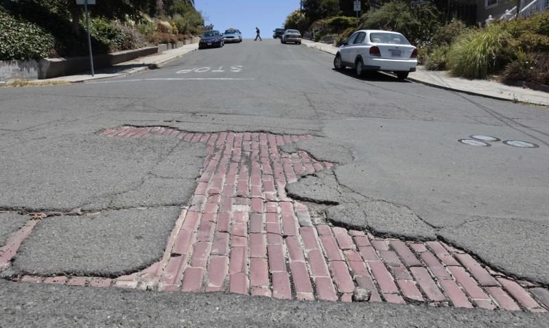 In this photo taken Thursday, July 19, 2012, cobblestones show through a hole in the pavement on Sutter Street in Vallejo, Calif. In 2008 Vallejo declared bankruptcy, forcing the reduction of many city services, like road repairs. Emerging from bankruptcy last year, the Vallejo offers an example for what can come, both good and bad, from the experience. Some in the community say bankruptcy was the city's only option to climb out of a financial hole while others say more could have been done to avoid it.(AP Photo/Rich Pedroncelli)