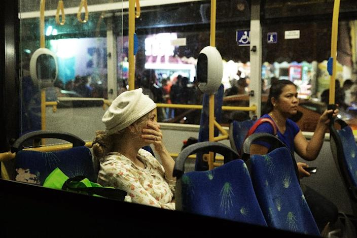A woman on a bus reacts after a knife-wielding man stabbed and wounded a woman near Jerusalem's central bus station on October 14, 2015 (AFP Photo/Menahem Kahana)