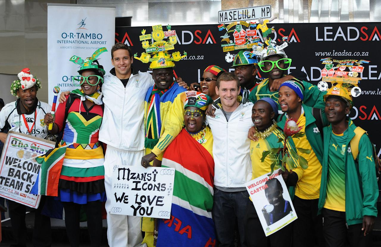 JOHANNEBSURG, SOUTH AFRICA - AUGUST 14: Medal winners Chad le Clos (3rd L) and Cameron van der Burgh pose with fans during the South African Olympic team arrival and press conference at OR Tambo International Airport on August 14, 2012 in Johannesburg, South Africa. (Photo by Duif du Toit/Gallo Images/Getty Images)