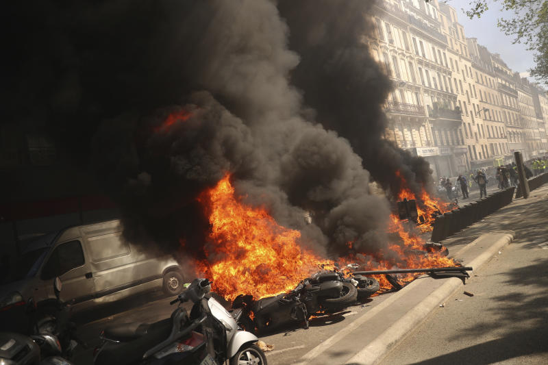 A set of motorbikes are set alight during a yellow vest demonstration in Paris, Saturday, April 20, 2019. French yellow vest protesters are marching anew to remind the government that rebuilding the fire-ravaged Notre Dame Cathedral isn't the only problem the nation needs to solve. (AP Photo/Francisco Seco)